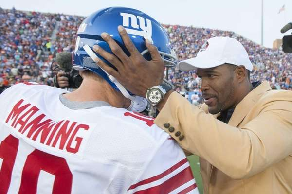 Giants quarterback Eli Manning talks with Michael Strahan