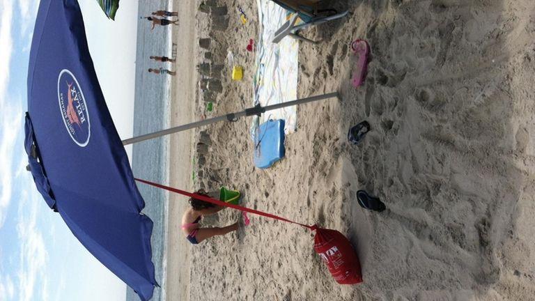 An umbrella anchored to a sandbag keeps everything