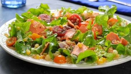 Lettuce is tossed with seared and flaked salmon,