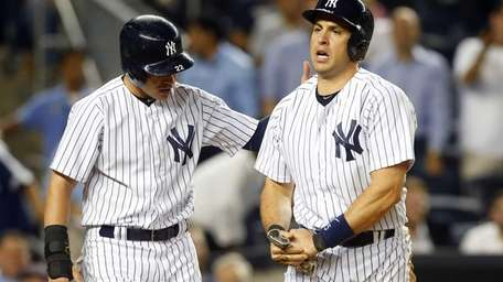 Mark Teixeira holds his wrist after scoring in