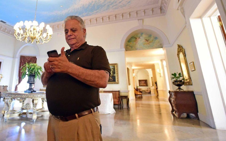 Gary Melius checks his cell phone at Oheka