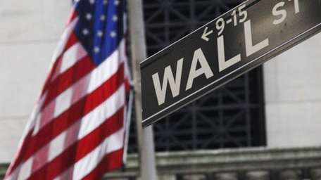 The American flag and Wall St. street sign