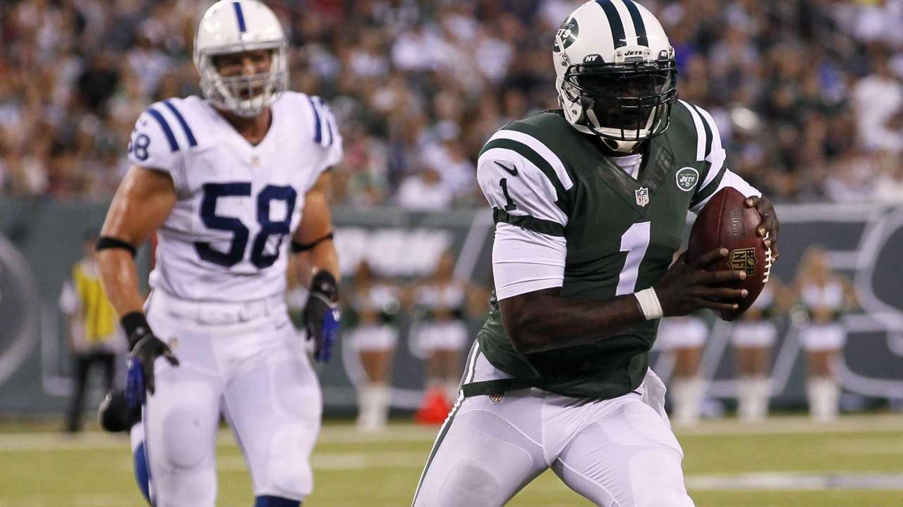 Jets quarterback Michael Vick (1) runs during a