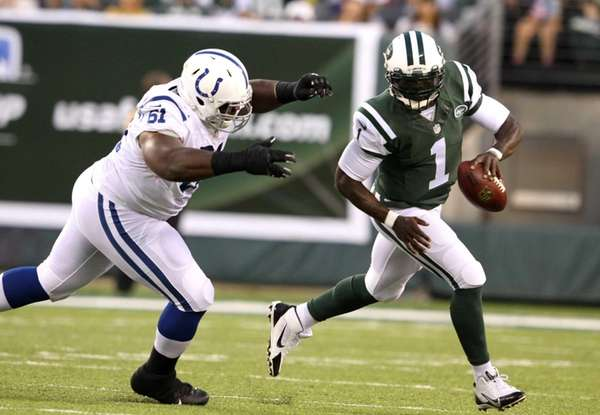 Jets quarterback Michael Vick (1) runs from an