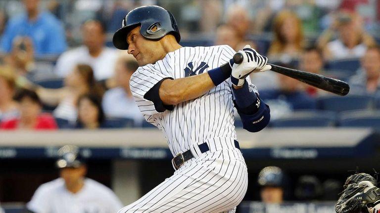 Derek Jeter of the Yankees follows through on