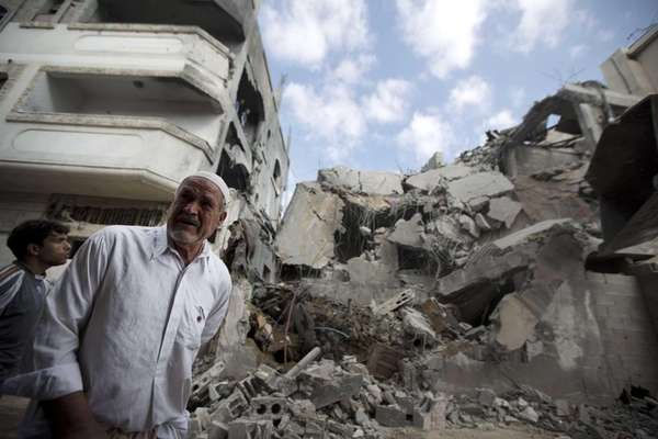Palestinian men inspect the remains of a building