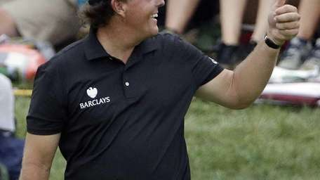 Phil Mickelson celebrates his eagle on the 18th