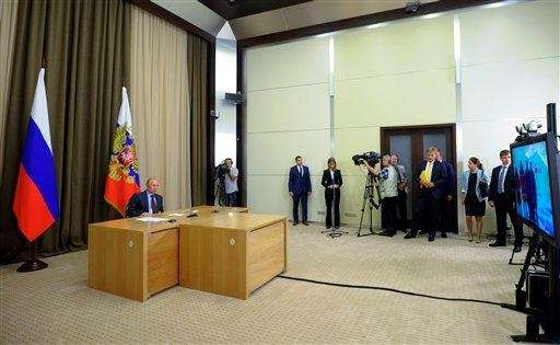 Russia President Vladimir Putin, left, prepares to give
