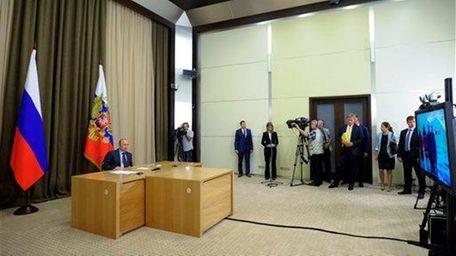 Russia President Vladimir Putin, left, prepares to give