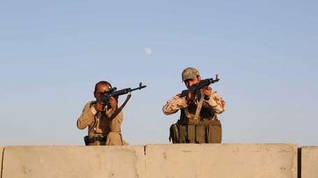 Kurdish peshmerga fighters stand guard during airstrikes targeting