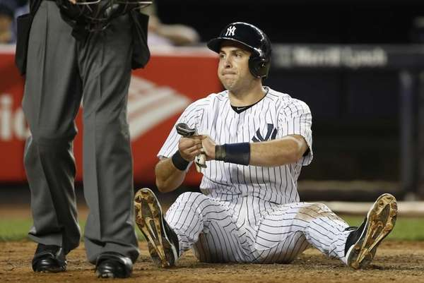 Mark Teixeira sits in the dirt after injuring