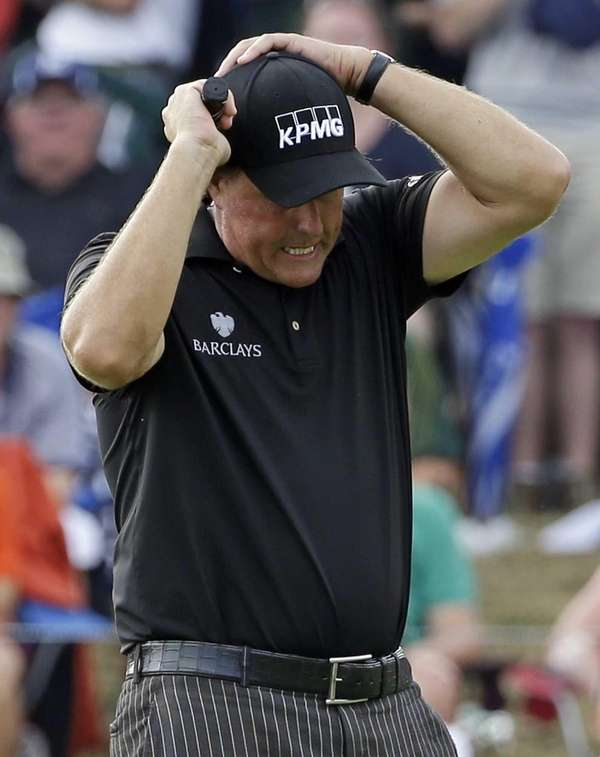 Phil Mickelson reacts after missing an eagle putt