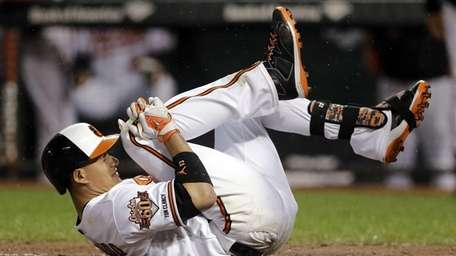 The Baltimore Orioles' Manny Machado reacts after grounding