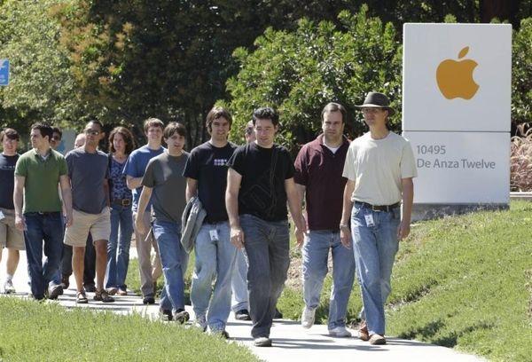 Apple employees walk between buildings on the Apple