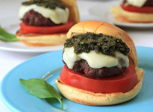 A Caprese burger with pesto and melted mozzarella.