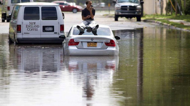 Herbert Scott, of Medford, sits atop his car