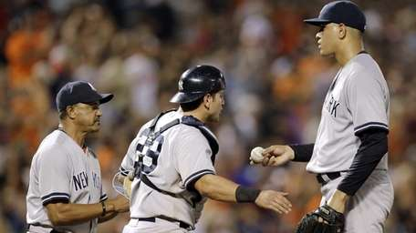 Yankees bench coach Tony Pena, left, relieves relief