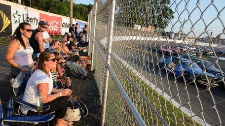 Family members and team members watch racers make