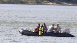 Police, rescue workers and divers work at the