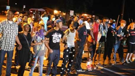 Demonstrators protest the shooting death of teenager Michael