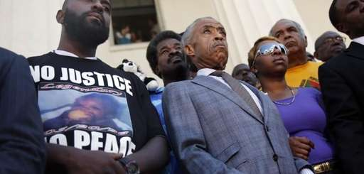 The Rev. Al Sharpton, center, stands with the