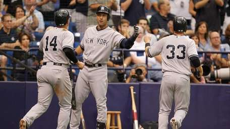 The Yankees' Derek Jeter celebrates with teammates after