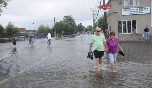 People walk through Islip's flooded Main Street Wednesday