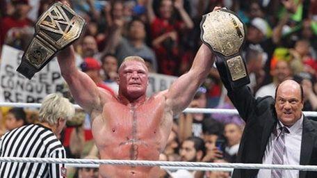 Brock Lesnar celebrates with Paul Heyman after winning