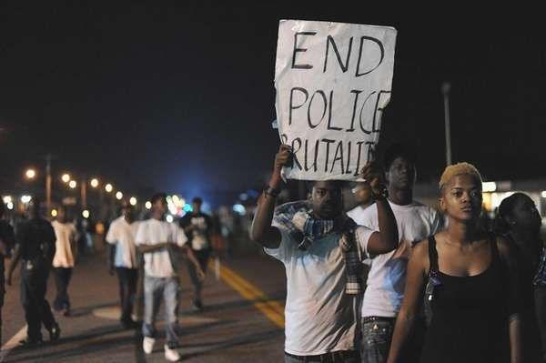 Demonstrators display signs during a protest on West