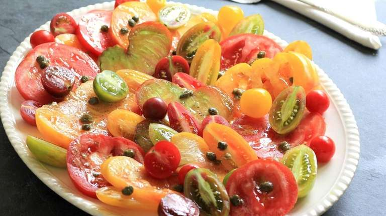 Mixed varieties of tomatoes are sliced or halved