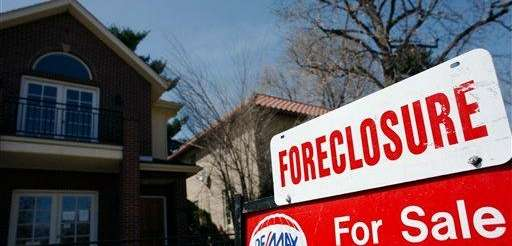 A foreclosure sign sits atop a for sale