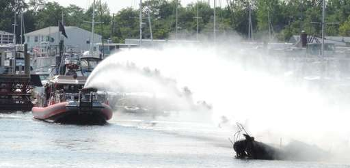 Emergency personnel spray down a boat that caught