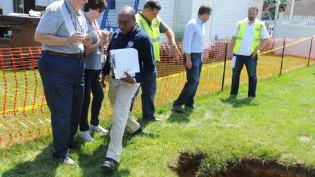 A FEMA official, left, with clipboard, walks past