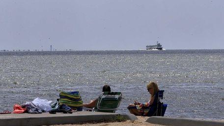 A couple relaxes at Bayport Beach near Homan