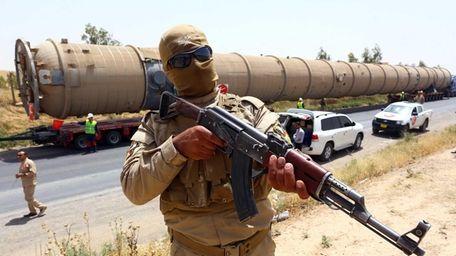 A Kurdish peshmerga fighter stands guard as new