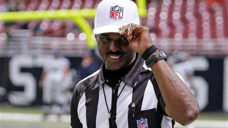 Referee Mike Carey tips his cap to the