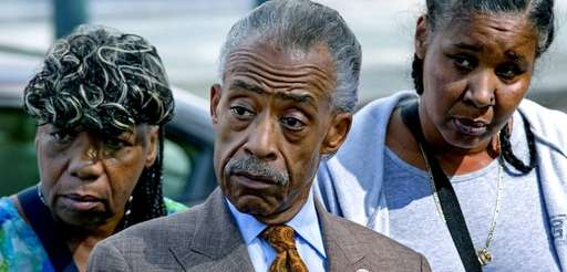 Rev. Al Sharpton, standing with Esaw Garner, wife