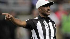 Referee Mike Carey calls a penalty during the
