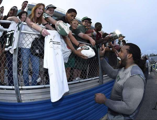 Jets guard Willie Colon signs autographs after practice
