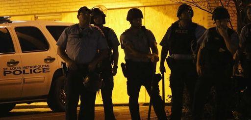 Police stand guard along Florissant Avenue in Ferguson,