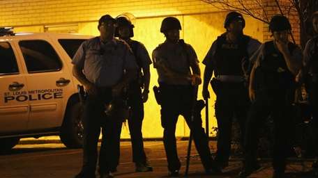 Police stand guard along Florissant Avenue in Ferguson,