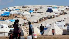 FILE: Refugees fill their buckets at the Atmeh