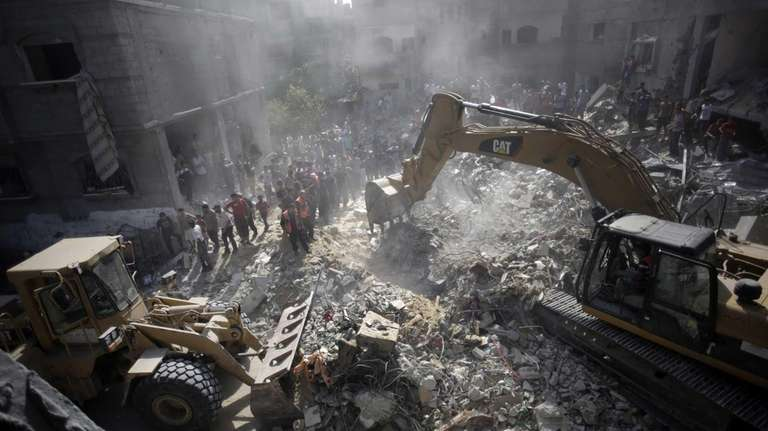 Palestinians gather around the rubble of a destroyed