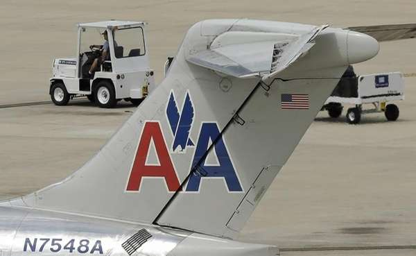 A ramp worker rolls past an American Airlines
