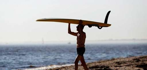 FILE: A windsurfer carries his board to the
