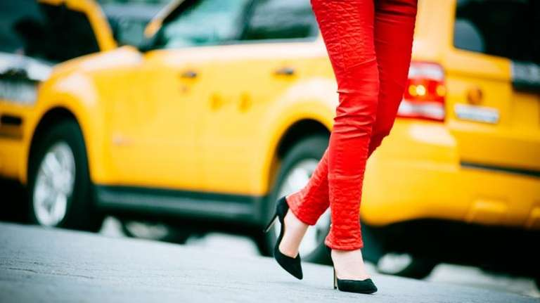 A woman in front of a cab.
