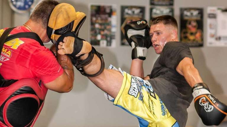 UFC fighter Chris Wade, right, hits pads with
