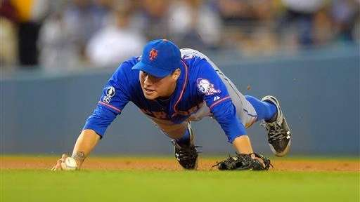 Mets shortstop Wilmer Flores trips while trying to