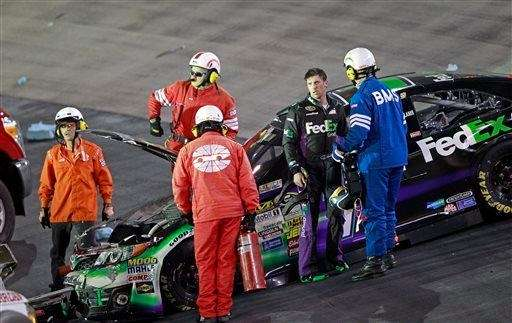 Denny Hamlin (11) is assisted by emergency personnel