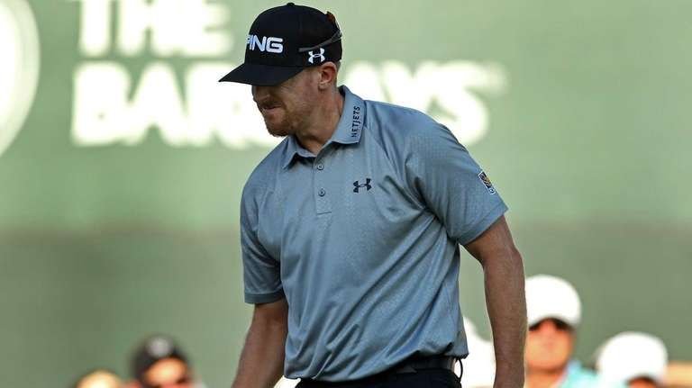 Hunter Mahan reacts after putting on the 17th